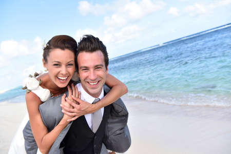 Groom giving piggyback ride to bride at the beach