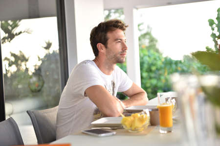Man sitting at breakfast table, waking-up