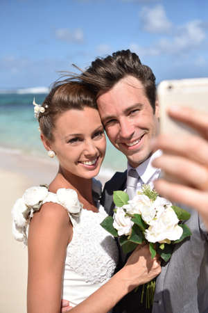 taking a wife: Just married couple at the beach taking selfie picture