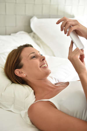 whiteness: Woman laying on bed and using smartphone Stock Photo