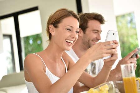 couple having fun: Couple having fun using smartphone at breakfast time