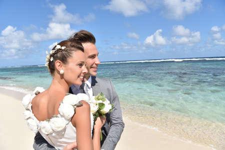 Gerade verheiratetes Paar auf den Strand auf die Skyline suchen