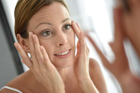 Woman applying facial cream on her face Standard-Bild