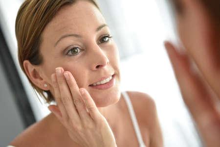 Woman applying facial cream on her face Stock Photo