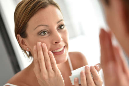 putting: Woman applying facial cream on her face Stock Photo