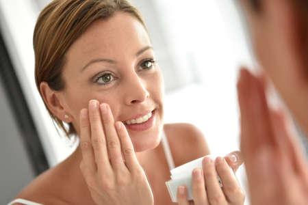 facial: Woman applying facial cream on her face Stock Photo