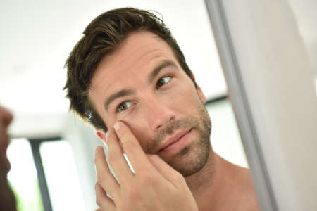 Knappe mens die gezichtsroom toepast voor spiegel Stockfoto