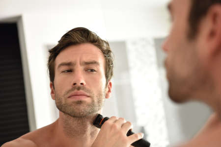 Handsome man in bathroom shaving with electric razor