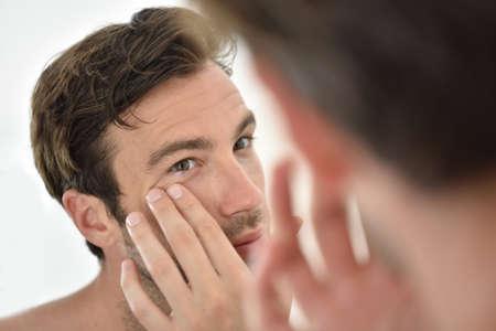 Hombre hermoso que aplica la crema facial en frente del espejo