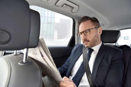 seatbelt: Businessman in taxi cab reading newspaper