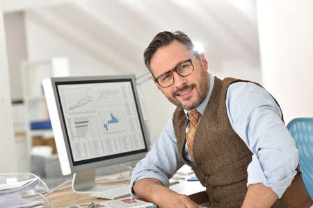 success man: Middle-aged businessman with eyeglasses in office Stock Photo