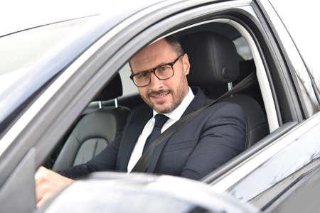 chofer: Retrato de la sonrisa conductor de taxi en coche de lujo