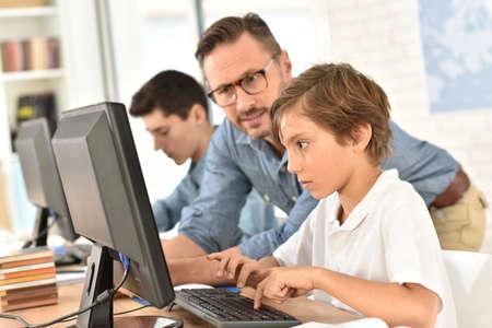 Leraar met kinderen in de informatica klasse