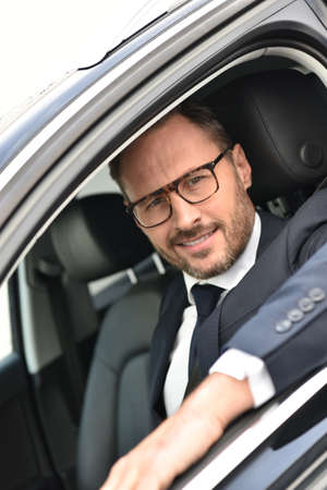 Portrait of smiling taxi driver in fancy car Stock Photo