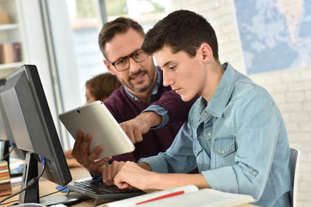Teacher in computing class assisting teenager with tablet