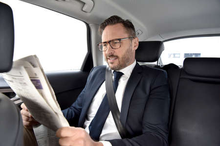 privilege: Businessman in taxi cab reading newspaper