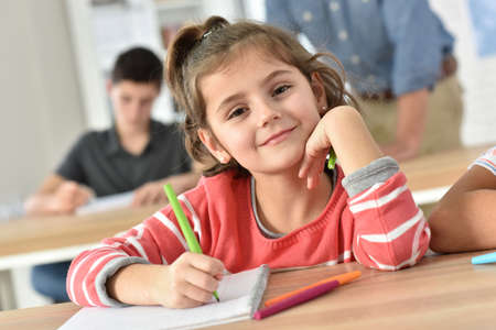 literacy: Cute schoolgirl in class writing on notebook