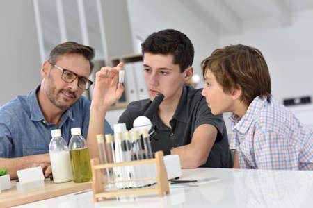 children at school: School boys with teacher in chemistry class