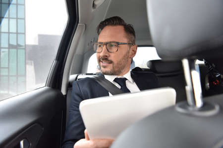 car service: Businessman in taxi cab reading new on digital tablet Stock Photo