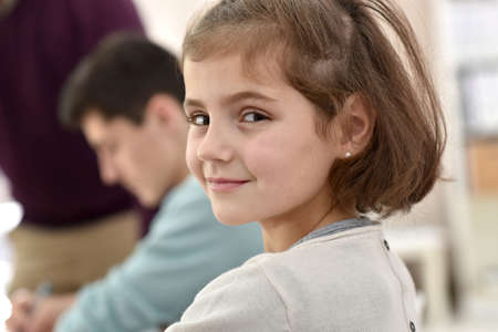 camera girl: Portrait of smiling school girl in class Stock Photo