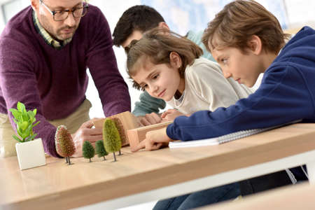 School teacher in science class with pupils