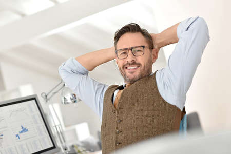 arms behind head: Businessman with eyeglasses relaxing in front of desktop
