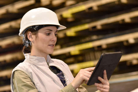 Woman in metal industry warehouse checking products