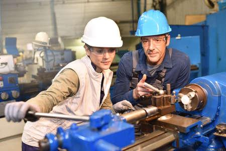 Metal trabajador docente en prácticas en el uso de la máquina