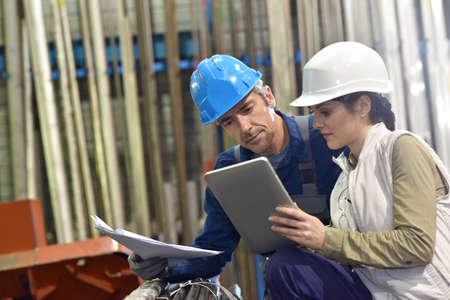 seguridad laboral: Ingenieros en almacén de la metalurgia utilizando tableta digital