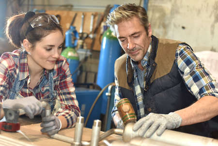 knowhow: Metal craftsman teaching know-how to young woman