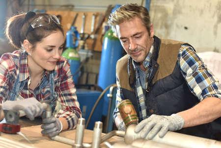 Metallo artigiano insegnamento know-how alla giovane donna