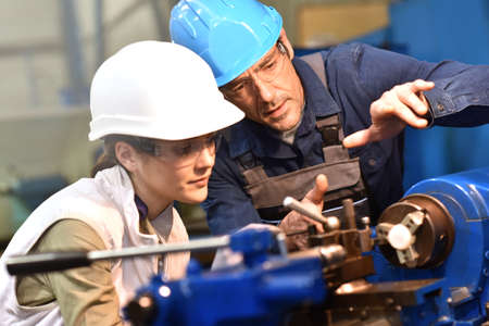 Metal worker teaching trainee on machine use Stock Photo