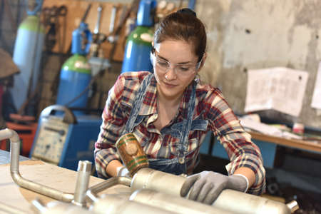 manufacture: Woman with protective glasses working in metallurgy workshop Stock Photo