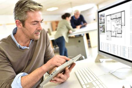 Inżynier pracujący w biurze projektowym na komputerze stacjonarnym