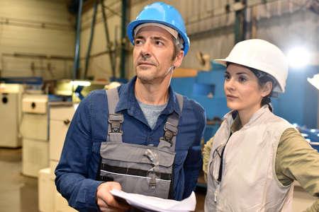 metal worker: Metal worker showing machine room to apprentice Stock Photo
