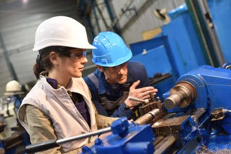 Metal trabajador docente en prácticas en el uso de la máquina Foto de archivo