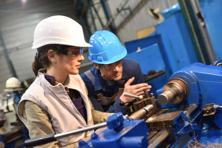 Metal worker teaching trainee on machine use Stockfoto