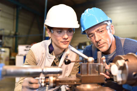 trainee: Metal worker teaching trainee on machine use Stock Photo