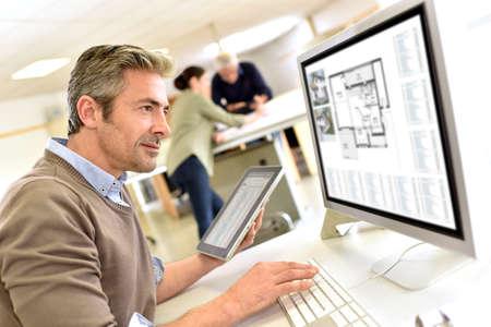 Ingegnere, lavorando in ufficio di progettazione su computer desktop Archivio Fotografico