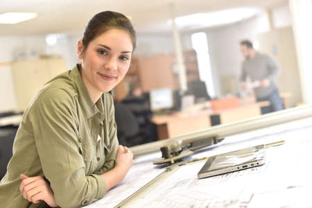 drawing table: Woman architect working on drawing table in office Stock Photo