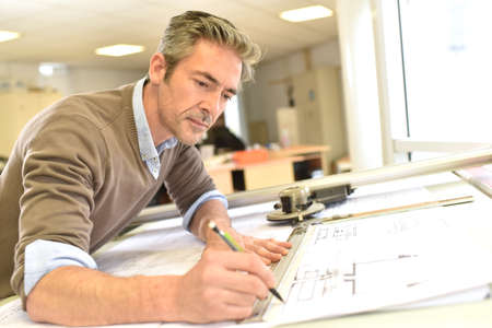 Architect working on drawing table in office Stockfoto