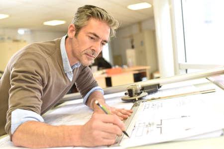 Architetto che lavora sul disegno tavolo in ufficio