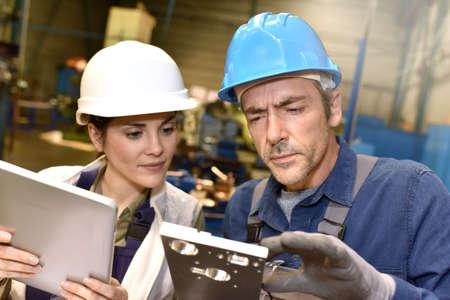 mujer trabajadora: Trabajadores metalúrgicos en el taller utilizando tableta digital