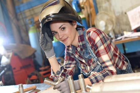 maquinaria: Mujer con la máscara protectora en el taller de la metalurgia