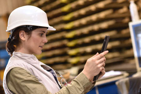 logistics: Woman in metal industry warehouse checking products