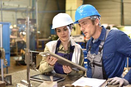 Metallurgy workers in workshop using digital tablet Foto de archivo