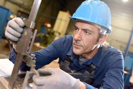 metal worker: Metal worker using machine in workshop
