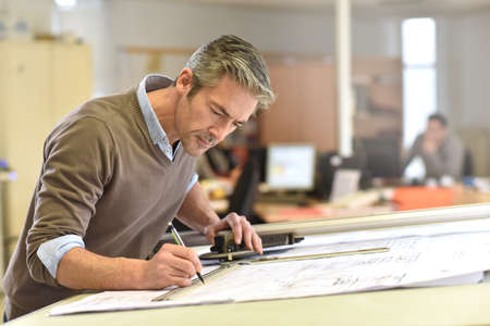 architect drawing: Architect working on drawing table in office Stock Photo