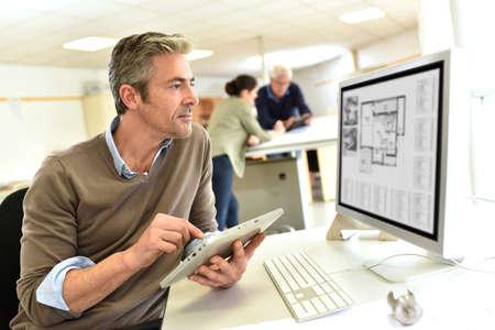 Ingegnere, lavorando in ufficio di progettazione su computer desktop