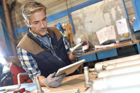 metal worker: Metal worker in workshop using digital tablet